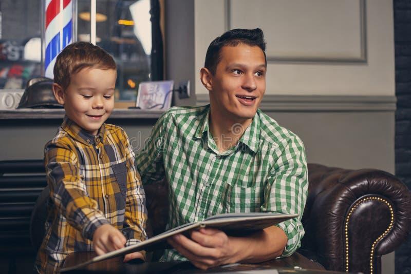Padre joven y su pequeño hijo elegante en la barbería en la sala de espera imagen de archivo