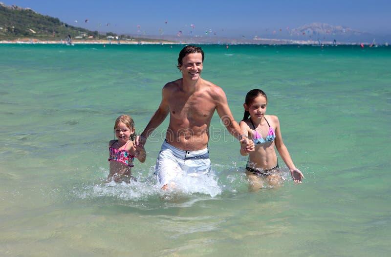 Padre joven y sus dos hijas el vacaciones fotos de archivo
