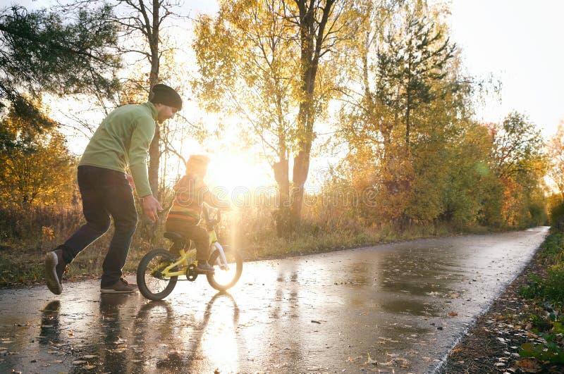 Padre le enseña a su pequeño a montar en bicicleta en el parque del otoño Felices momentos familiares Tiempo juntos padre e hijo  fotos de archivo
