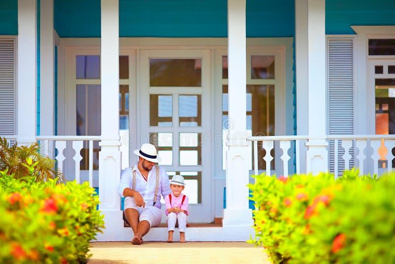 Padre lindo e hijo que se sientan en el pórtico, exterior del Caribe imagen de archivo