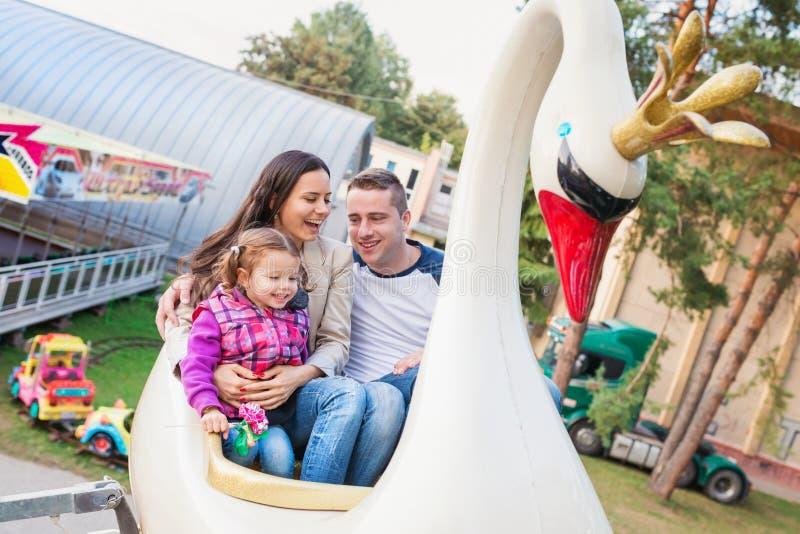 Padre, madre, hija que disfruta del paseo de la feria de diversión, parque de atracciones foto de archivo