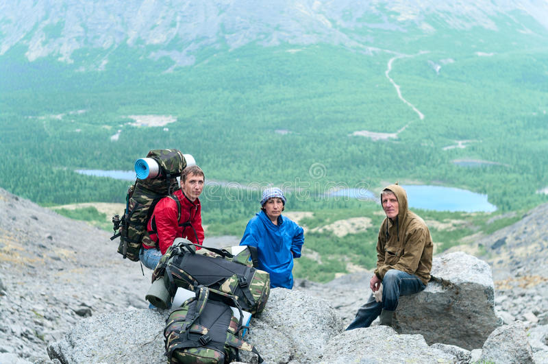 Padre, madre madura e hijo caminando en montañas junto imagenes de archivo