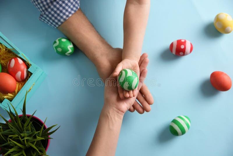 Padre, madre y su niño sosteniendo el huevo de Pascua pintado en fondo del color imagen de archivo