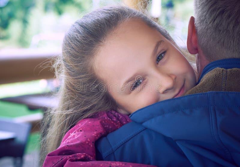 Padre maduro abrazado por su hija, sonriendo y riendo junto del café de la terraza Momentos felices de la familia, padre imagen de archivo libre de regalías