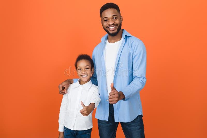 Padre milenario And Cute Daughter del Afro que muestra los pulgares para arriba fotografía de archivo libre de regalías