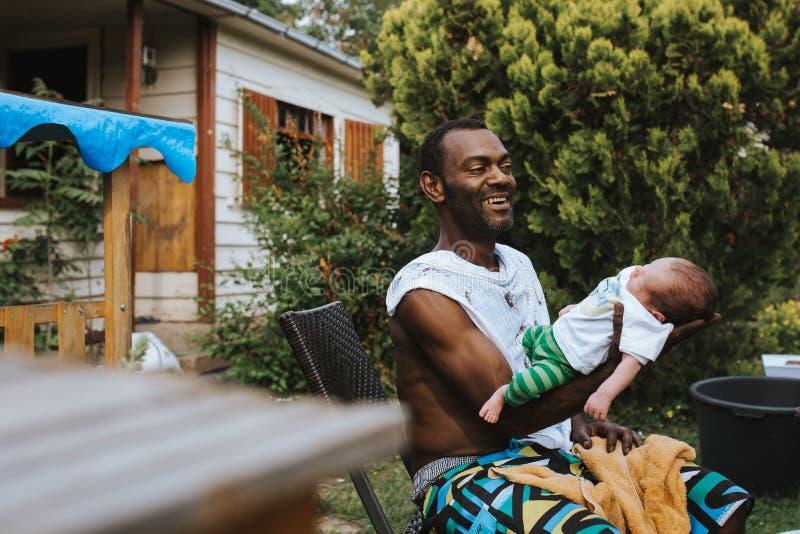 Padre nero che tiene e che ride di suo figlio neonato fotografia stock