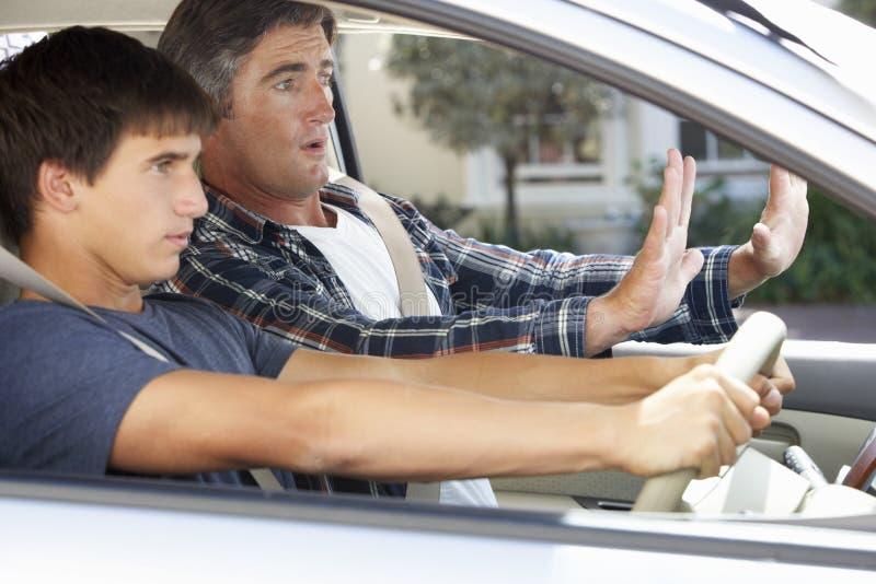 Padre nervioso Teaching Teenage Son a conducir foto de archivo