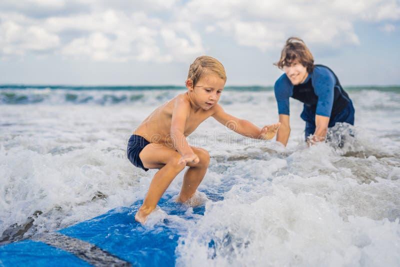 Padre o istruttore che insegna a suo figlio di 4 anni a come praticare il surfing dentro immagini stock libere da diritti