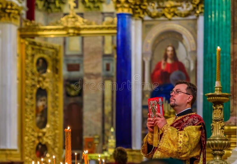 Padre ortodoxo do russo na roupa tradicional que serve na catedral ortodoxo do russo do Isaac de Saint em St Petersburg Russi fotos de stock