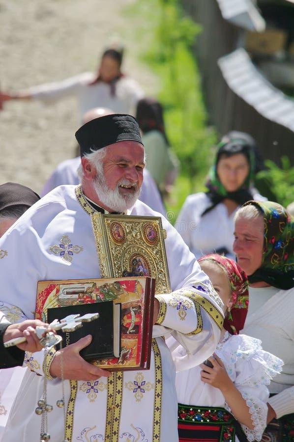 Padre ortodoxo e povos em trajes nacionais tradicionais - uma vila em Maramures, Romênia imagem de stock
