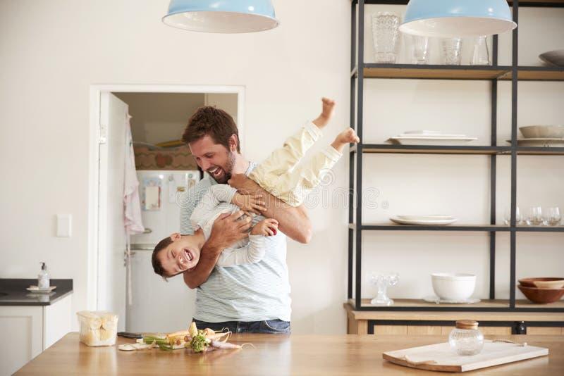 Padre Playing With Son como preparan la comida en cocina fotografía de archivo libre de regalías