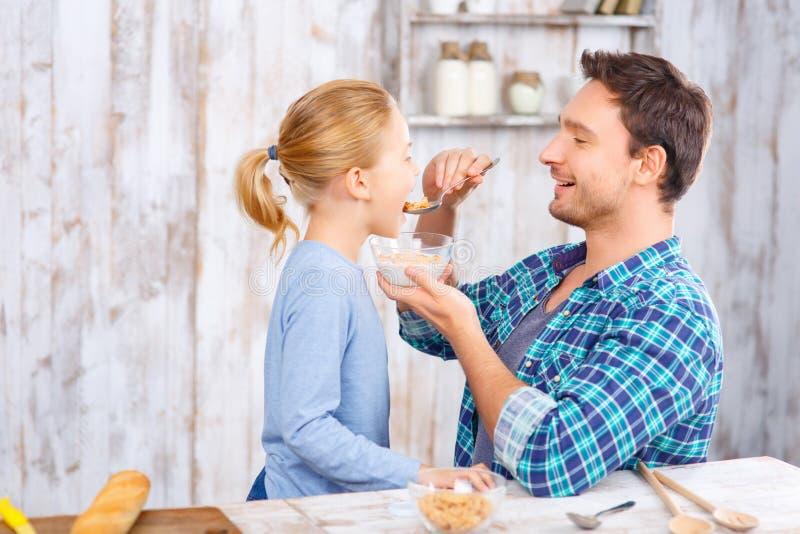 Padre positivo e figlia che mangiano prima colazione fotografia stock libera da diritti