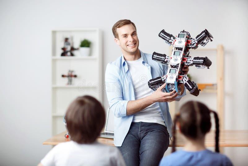 Padre positivo que sostiene el robot foto de archivo