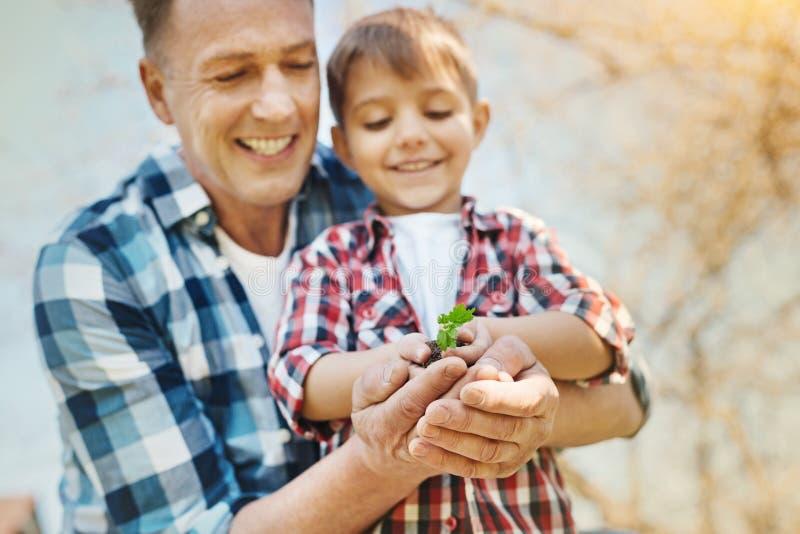 Padre positivo y su hijo que sostienen un puñado de suelo imagen de archivo libre de regalías