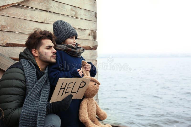 Padre povero e bambino con il segno di AIUTO alla riva del fiume immagine stock libera da diritti