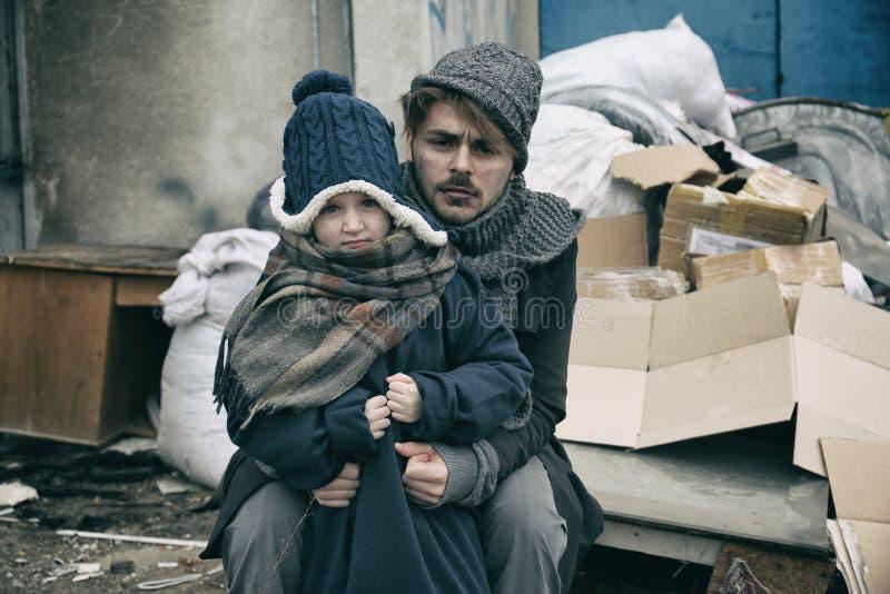 Padre povero e bambino vicino ad immondizia immagini stock libere da diritti