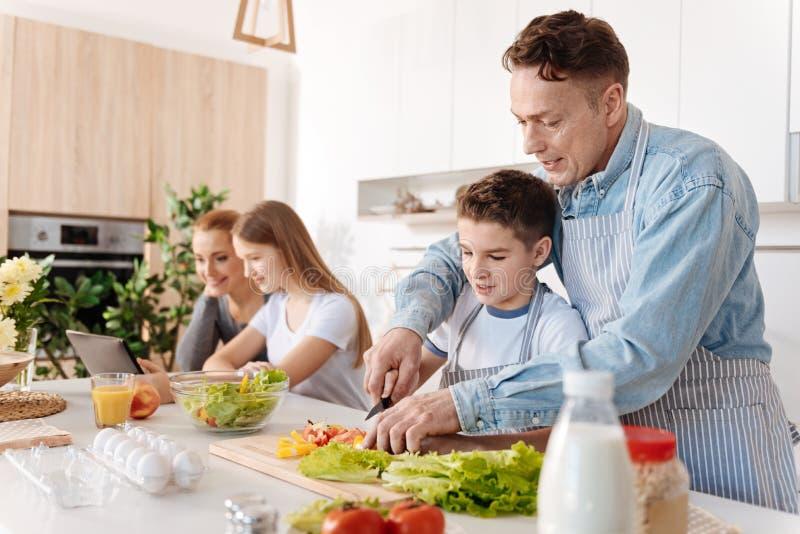 Padre preoccupantesi che insegna al suo piccolo figlio alle tecniche culinarie immagini stock