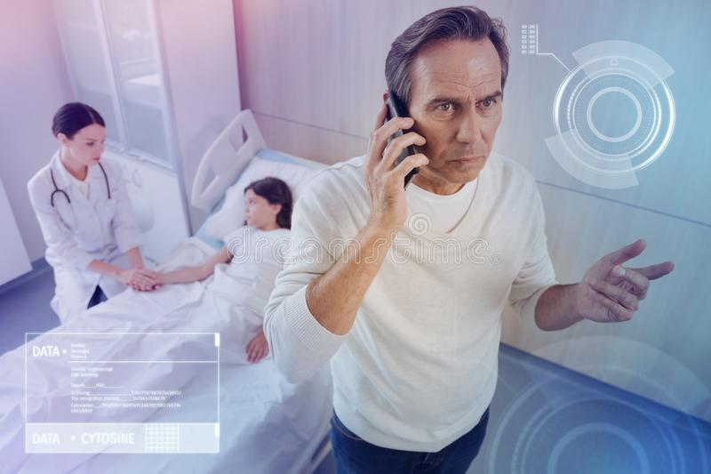 Padre preocupante que tiene una charla del teléfono mientras que visita a su hija enferma en un hospital foto de archivo