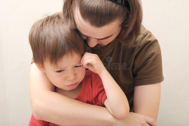 Padre que abraza al hijo gritador fotografía de archivo libre de regalías