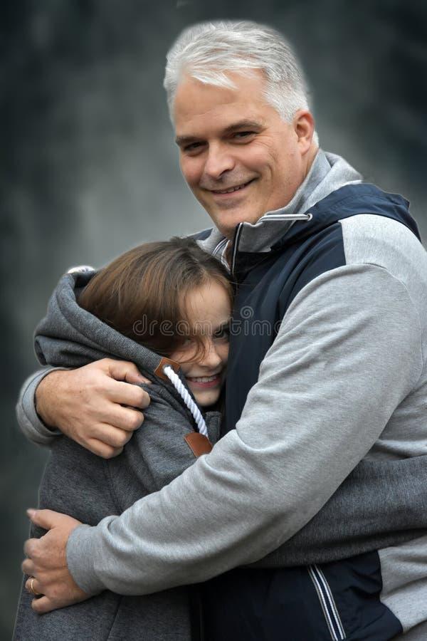 Padre que abraza a su hija adolescente fotografía de archivo libre de regalías