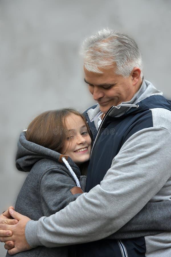 Padre que abraza a su hija adolescente fotos de archivo libres de regalías
