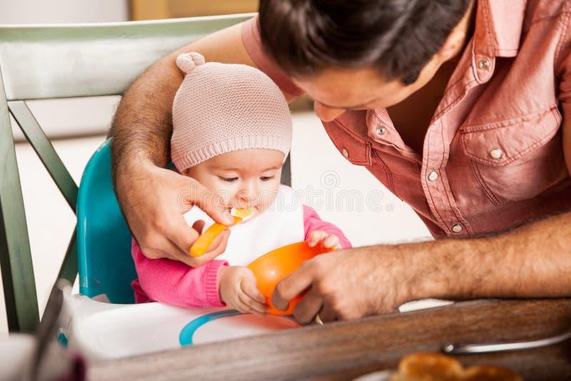 Padre que alimenta a su bebé en casa imagenes de archivo