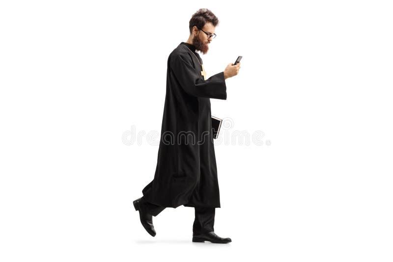 Padre que anda com um telefone celular imagem de stock royalty free