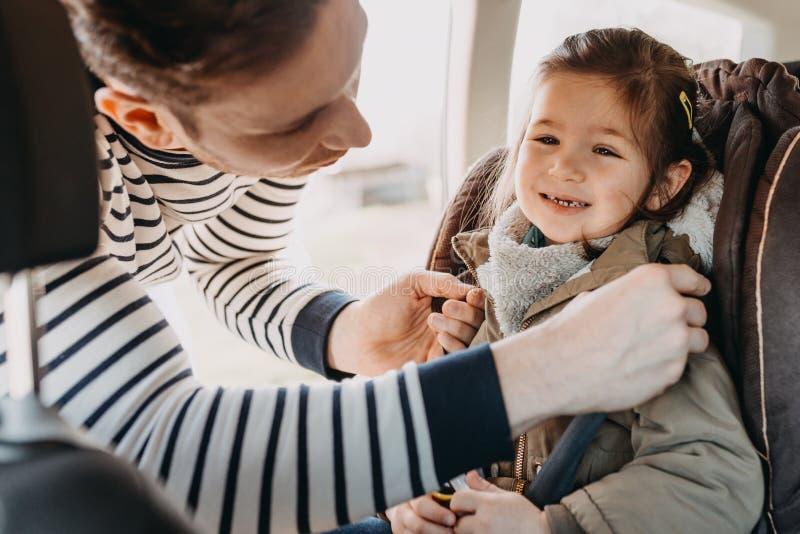 Padre que asegura a su hija del niño abrochada en su asiento de carro del bebé imagen de archivo libre de regalías