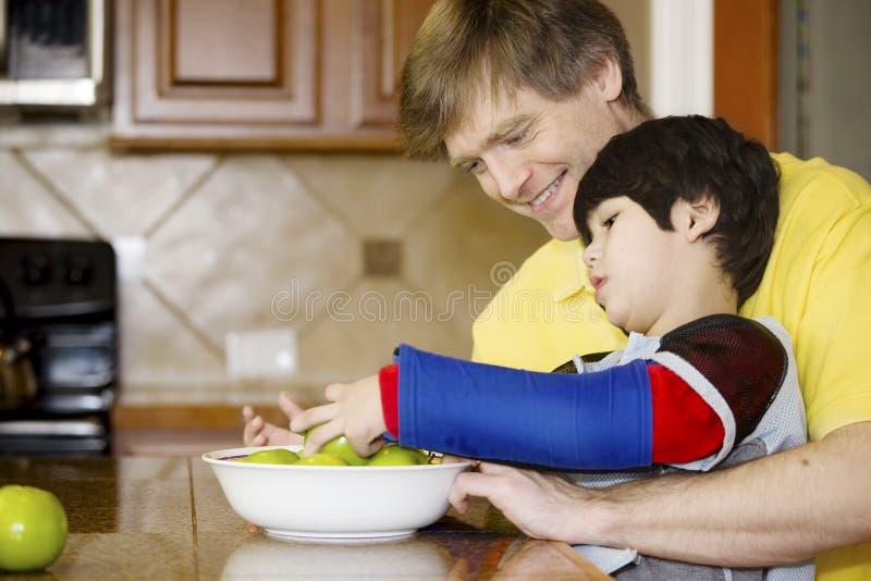 Padre que ayuda al hijo invalidado en la cocina fotografía de archivo