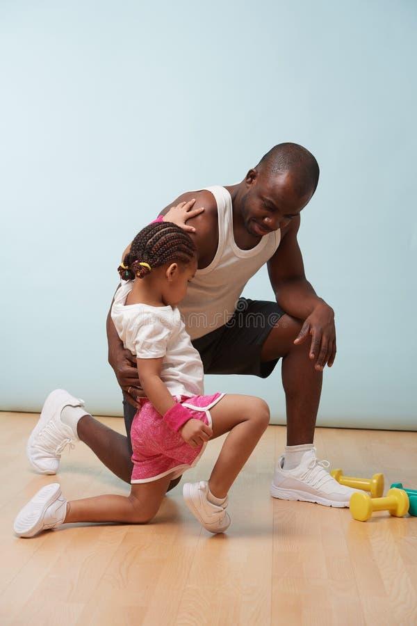 Padre que ayuda a su pequeña hija a hacer ejercicios físicos en casa fotos de archivo