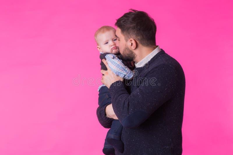 Padre que besa a su hijo en fondo rosado En estudio foto de archivo libre de regalías