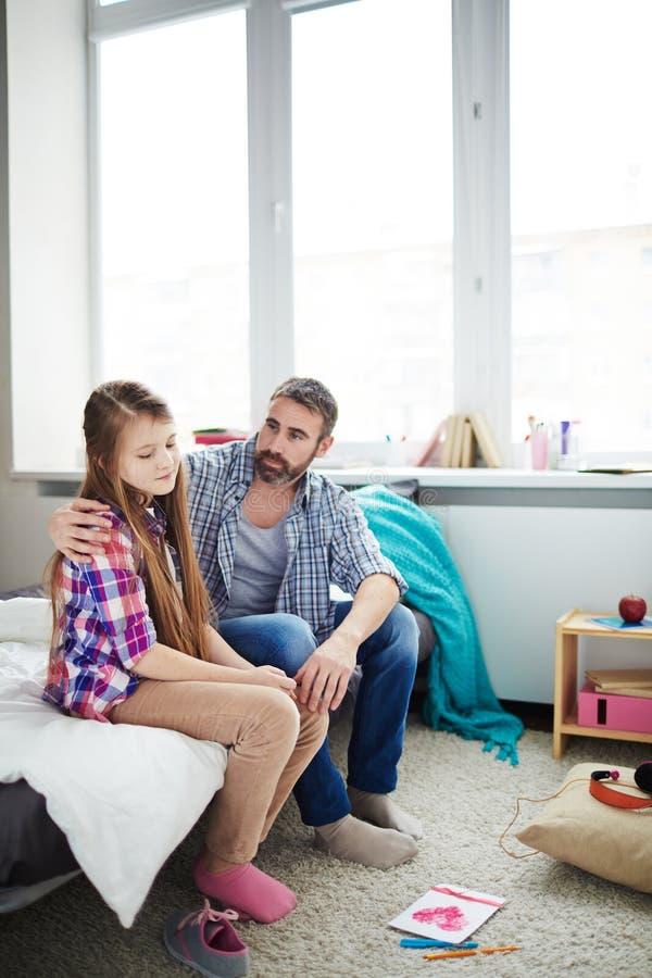 Padre que conforta a su hija adolescente fotografía de archivo