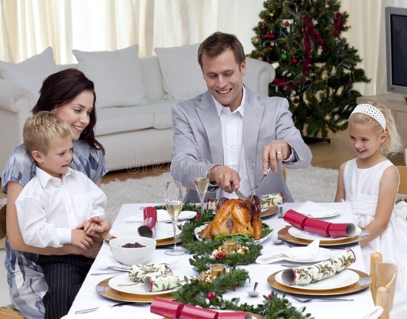 Padre que corta un pavo en cena de la Navidad
