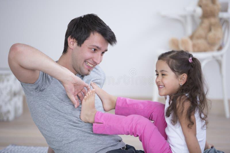 Padre que cosquillea el pie de la hija en casa fotos de archivo libres de regalías