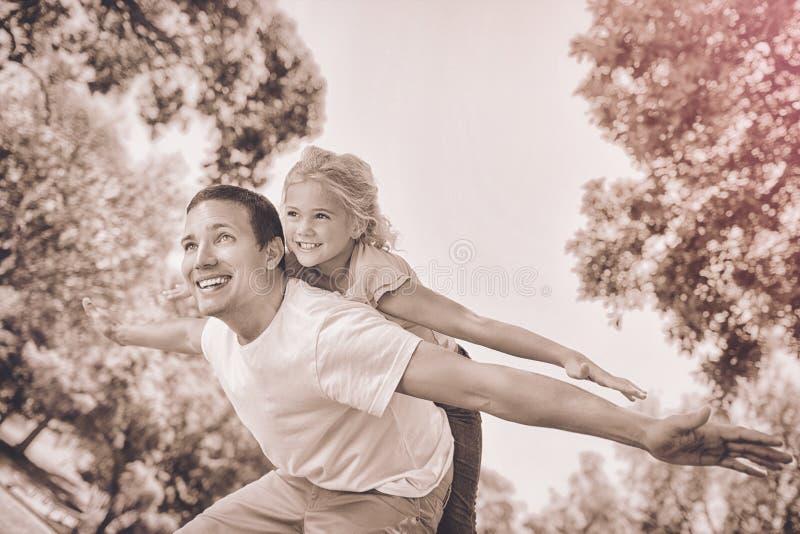 Padre que da a hija un transporte por ferrocarril en parque imagen de archivo libre de regalías