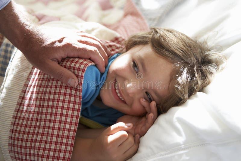 Padre que despierta al muchacho joven dormido en cama fotografía de archivo