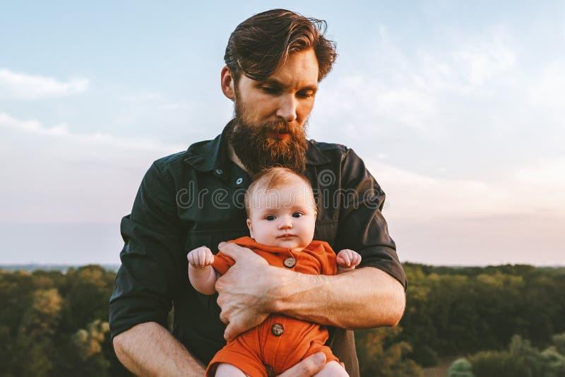 Padre que detiene al beb? infantil que camina junto al aire libre imagen de archivo libre de regalías