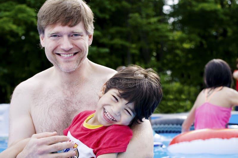 Padre que detiene al hijo invalidado en piscina fotografía de archivo