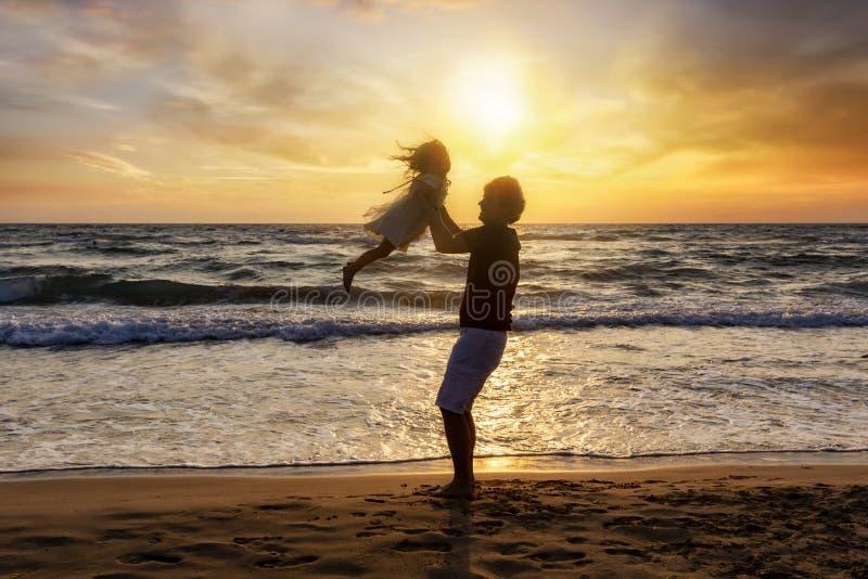 Padre que detiene a su hija en el aire en la playa fotografía de archivo