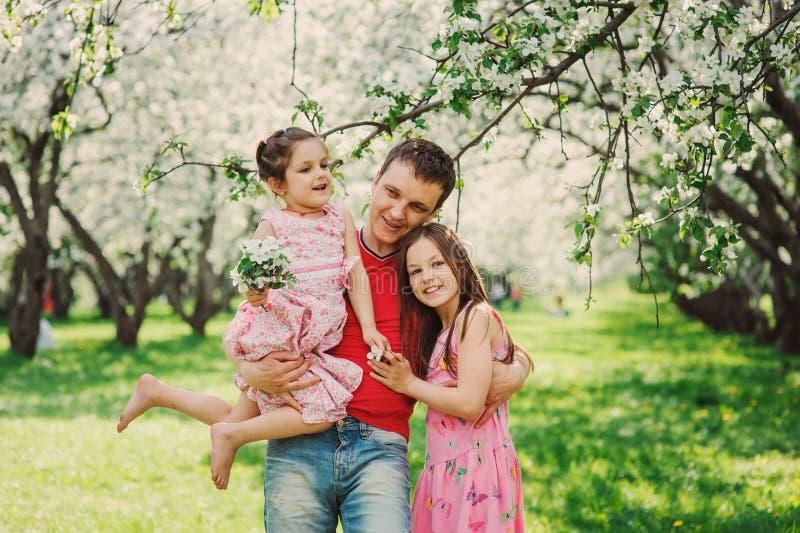 Padre que disfruta del paseo de la primavera con dos hijas sonrientes del niño foto de archivo
