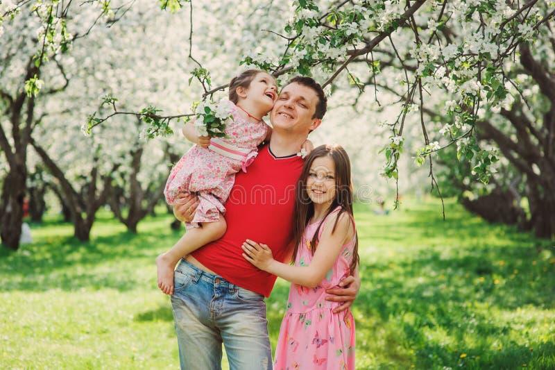 Padre que disfruta del paseo de la primavera con dos hijas sonrientes del niño imagen de archivo