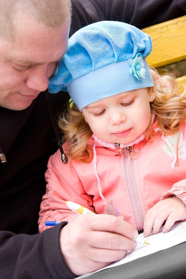 Padre que enseña a la pequeña hija a escribir imagen de archivo