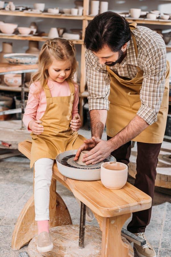 padre que enseña a su hija a utilizar la rueda de la cerámica fotos de archivo