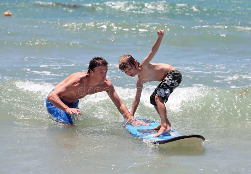 Padre que enseña a su hijo joven a practicar surf imagen de archivo