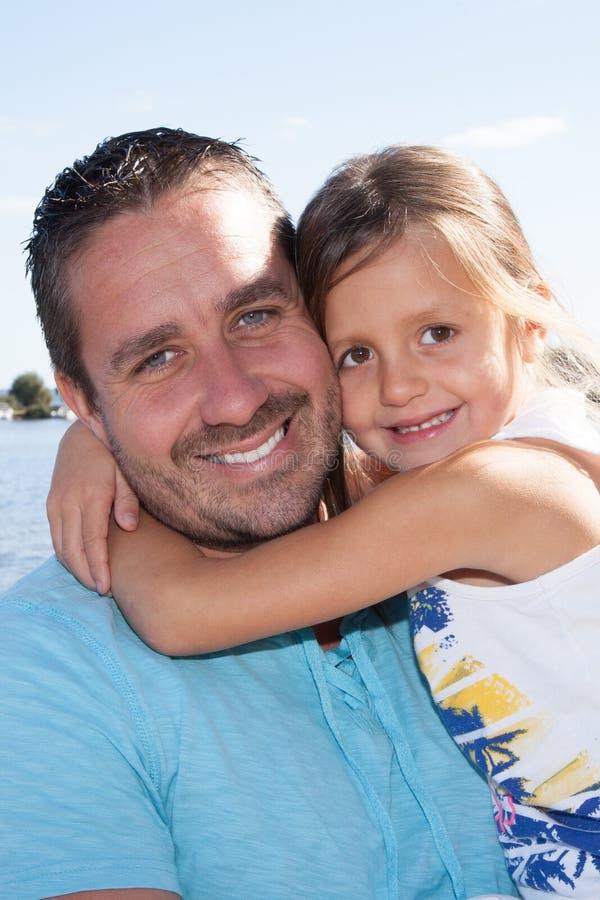 Padre que es abrazado por la hija de la niña imagen de archivo