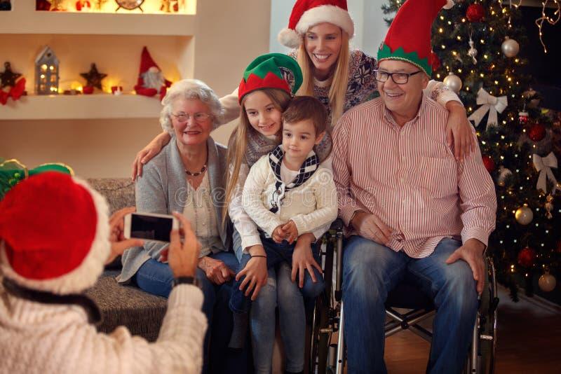 Padre que fotografía a la familia con el smartphone para la Navidad imagenes de archivo