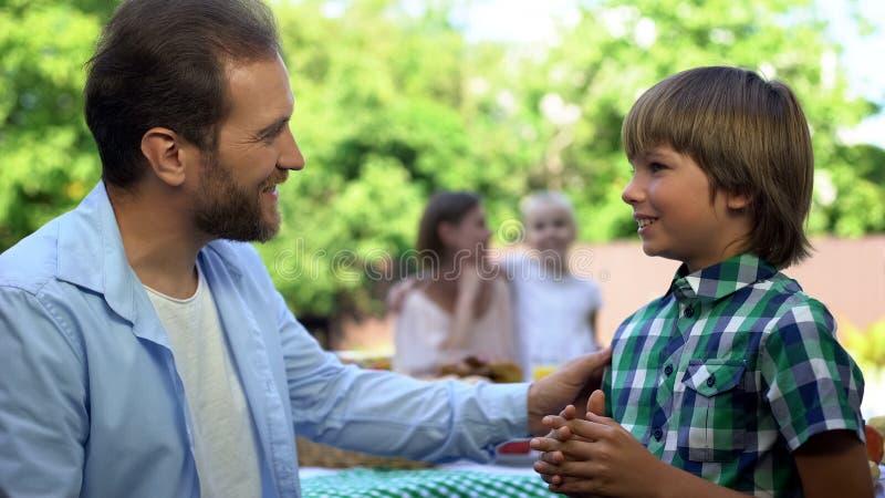 Padre que habla con el hijo, mamá que habla con la hija en el fondo, paternidad fotografía de archivo