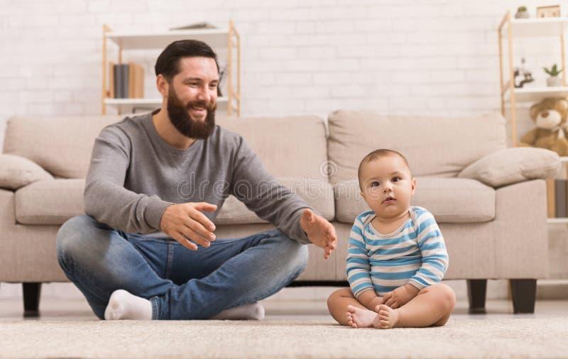 Padre que juega con su hijo del bebé en piso en casa imagen de archivo libre de regalías