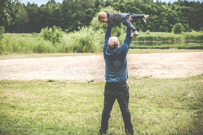 Padre que juega con su niño al aire libre, vuelo imagen de archivo