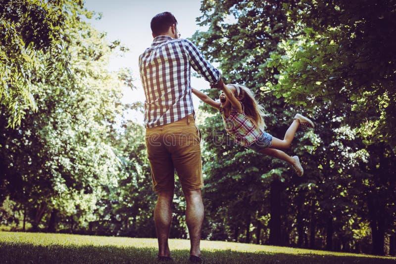 Padre que juega en el prado con la hija Goce en s foto de archivo libre de regalías